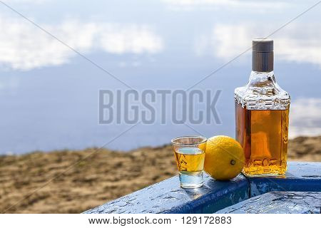 Bottle tequila and tumbler with lemon on shore of lake