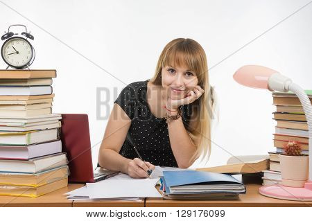 She Is Engaged At The Table Cluttered With Books In The Library With A Smile Looks In The Frame