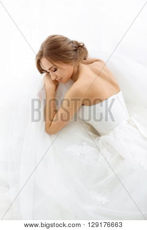 Beautiful young bride in white wedding dress indoors.  Luxuty model lying and sleeping over white backgroung. Girl waiting her groom in bright room. Beautiful wedding hairdress. High key photo.