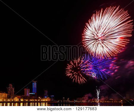 fireworks over night city and city pond Yekaterinburg city center. Celebrating the victory of May 9, 2016