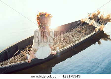 Young sexy woman on boat at sunset. The girl has a flower wreath on her head, relaxing and sailing on river. Fantasy art photography. Concept of female beauty, rest in the nature, and water travel.