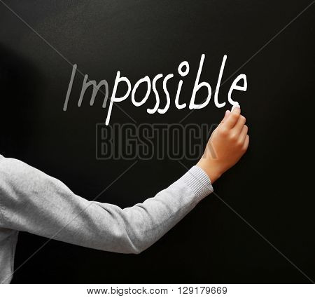 Hand writing word impossible transformed into possible  on blackboard
