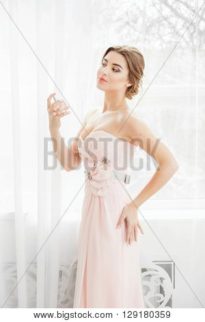 Beautiful young bride with wedding makeup and hairstyle in bedroom, newlywed woman final preparation for wedding. Happy Bride waiting groom. Marriage Wedding day moment.  Apply perfume.