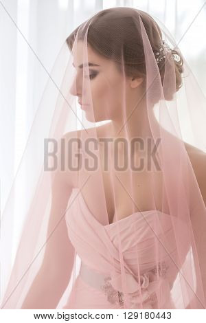 Portrait of a woman. Bride with a pink veil. Final preparations for the wedding.