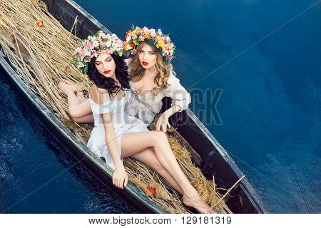 Two young women on boat at sunset. The girls has a colorfull make-up and flower wreath on they head, relaxing and sailing on the river. Beautiful sexy slim body and cute face. Fashion art photography. Concept of female beauty, rest on the nature, and wate
