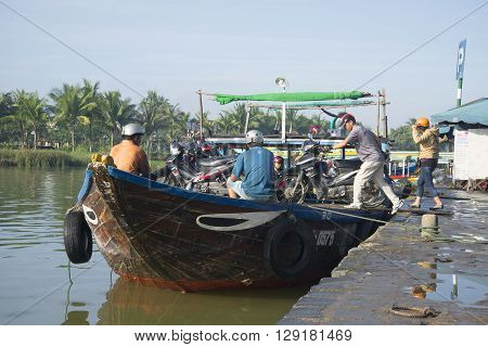 HOI AN, VIETNAM - JANUARY 04, 2016: Urban wooden ferry at the pier. People after the working day crossed by ferry across the river to the other side, Hoi An, Vietnam