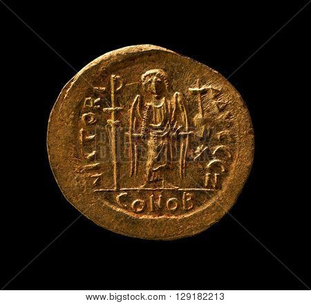 Ancient golden Byzantine coin with angel on it closeup macro shot