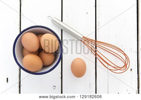 Eggs in a ceramic bowl with a wisk on a rustic white painted wood table top shot from above