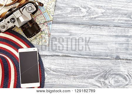 Vacation and travel items. Travel concept - camera map hat on a wooden background