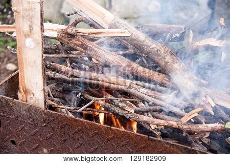 Wood burning in a barbeque grill. Closeup of firewood burning in fire.