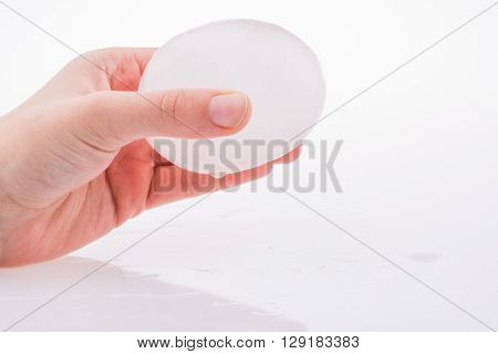 Hand holding an ice ball on a white background