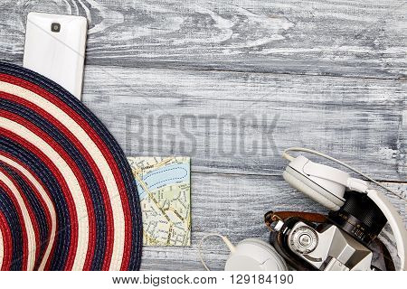 Vacation and travel items. Travel concept - headphones camera telephone map hat on a wooden background