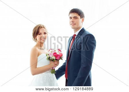 Happy wedding couple in love. Beautiful bride in white dress with brides bouquet and handsome groom in blue suit standing looking to the camera indoors at home against big window, white bright background