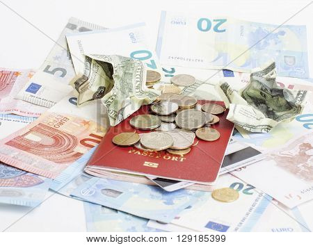 Travel on vacation lifestyle concept: cash money on table in mess with passport and change, travelers stuff