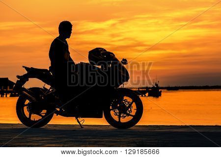 Silhouette of biker on his motorcycle at sunset looking to beautiful sunset sky
