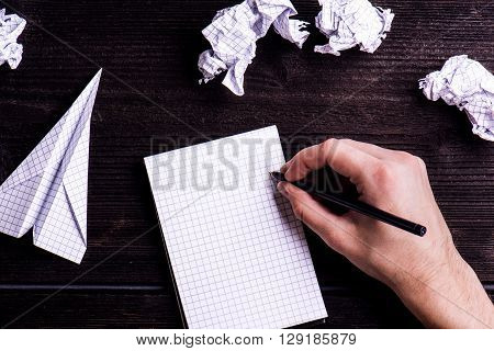 Hands of unrecognizable man writing on squared piece of paper, crumpled paper balls, paper airplane. Flat lay. Workplace. Studio shot on dark wooden background.