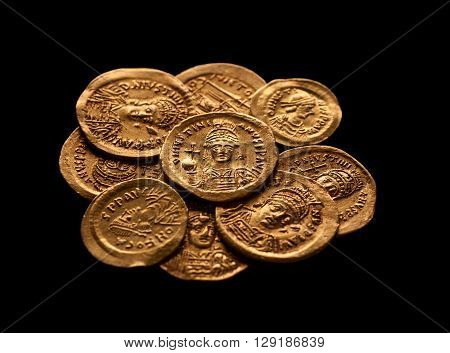 Pile of ancient golden Byzantine coins isolated on black selective focus closeup