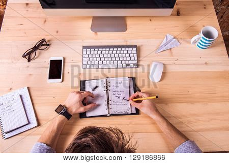 Businessman at the desk, wearing smart watch, writing into personal organizer.  Computer, smart phone and various office supplies around the workplace.
