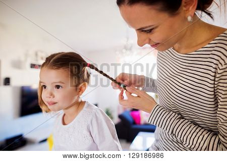 Beautiful young mother braiding hair of her little daughter in the morning