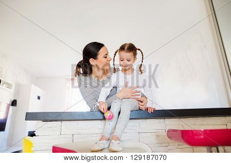 Beautiful young mother with her little daughter with braided hair in the morning