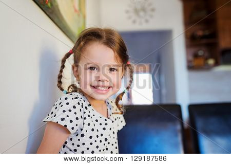 Cute little girl with two braids in dotted t-shirt smiling