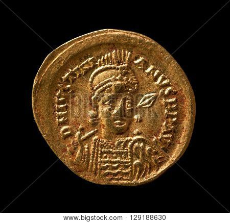 Ancient golden Byzantine coin with portrait of emperor closeup macro shot