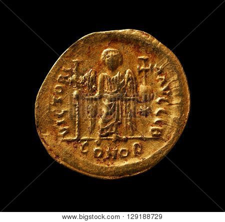 Ancient golden Byzantine coin with angel closeup macro shot