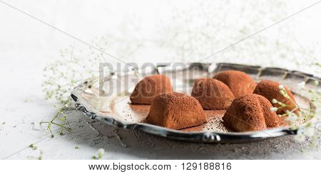 Handmade candies Tiramisu in eart shape on metal plate. Valentine's Day and Mother's Day concept with copy space.