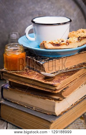 some pieces of pie with apricot jam and milk on old book
