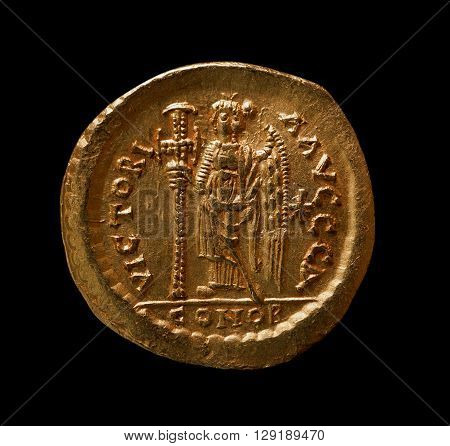 Ancient gold Byzantine coin of emperor Zenon reverse closeup shot isolated on black