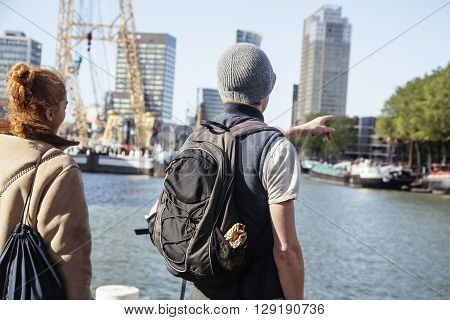 Young couple tourists looking and pointing to Rotterdam city harbour, future architecture concept, industrial lifestyle close up