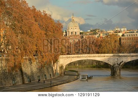 ROME, ITALY - DECEMBER 7: Autumnal panorama along River Tiber waterfront at sunset, with its typical plane-tree, in the center of Rome DECEMBER 7, 2014 in Rome, Italy