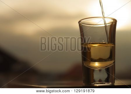 A shot of an alcohol beverage being poured