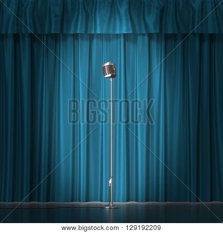 Retro silver microphone on blue cloth background.