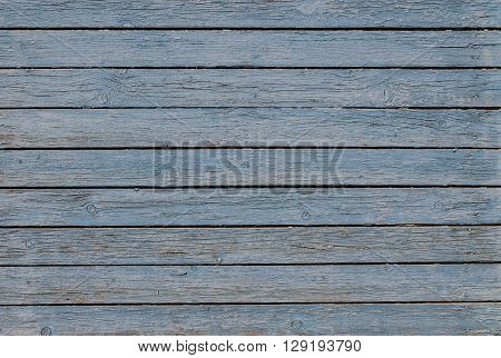 Wooden background with peeling blue paint horizontal boards