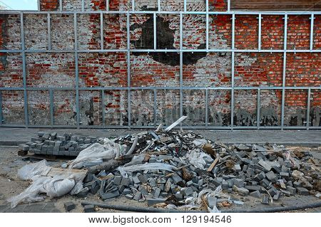 Repair of old brick wall. Mounting new surface on aluminium rails. Construction installation