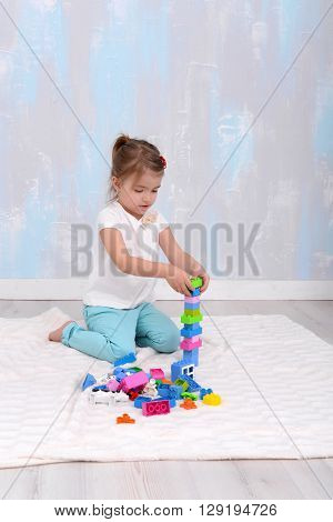 Child girl playing with toys constructor. vertical photo