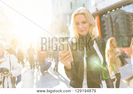 Blonde woman looking at smart phone in London at sunset. She is on her early forties she looks candid and spontaneous. Backlight shot with blurred people on background.