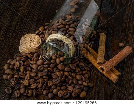 Coffee in a vintage jar, cinnamon  on wooden table, closeup