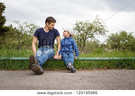 Happy father and son sitting in the park. Smiling young man spending time together with his son