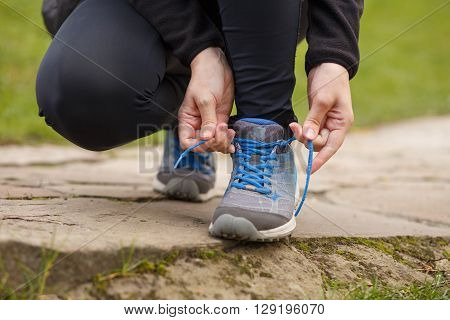 Sportswoman lacing up her running trainers. Fitness girl tying lace of her shoes for jogging