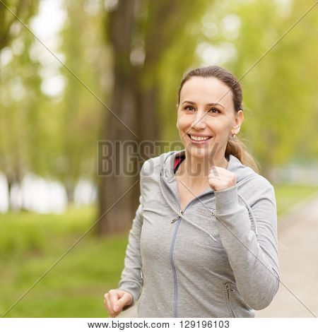 Young Smiling Woman Jogging In Park In The Morning