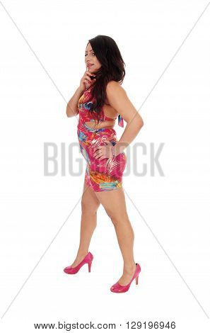 A beautiful young East Indian woman in a colorful summer dress standing in profile in high heels isolated for white background.