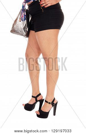 A closeup image of the legs and butt of a young woman holding her handbag and in high heels isolated for white background.