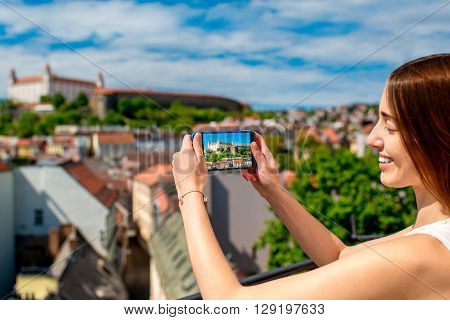Young female tourist photographing Bratislava castle from Michael's tower in Slovakia. Having fun traveling Slovakia