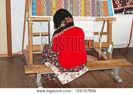 ANTALYA, TURKEY - MAY 02, 2012: Local woman weaves a carpet by hand in Antalya, Turkey. This low-tech method has remained unchanged for centuries