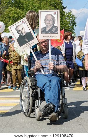 ULYANOVSK, RUSSIA - MAY 9, 2016: A disabled person in wheelchair holds portraits of relatives in the Immortal regiment on 9 May, 2016 in Ulyanovsk, Russia