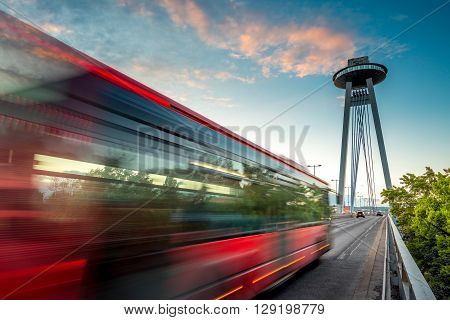 View on the Modern bridge with observation deck and restaurant called UFO in Bratislava city at the sunset. Long exposure technique with motion of cars