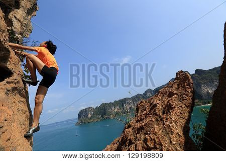 young woman rock climber climbing on seaside mountain cliff