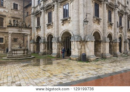 MONTEPULCIANO,ITALY-APRIL 23,2016:people stroll under the rain in the town square of Montepulciano during a cloudy day.